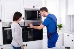 Mannelijke Technicus Fixing Oven stock fotografie