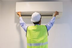 Mannelijke technicus schoonmakende airconditioner binnen royalty-vrije stock afbeeldingen