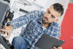Mannelijke Technicus Sitting Near Dishwasher die op Klembord in Keuken schrijven royalty-vrije stock foto's