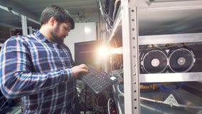 Mannelijke IT Technicus Working in de fabriek van de cryptocurrencemijnbouw stock footage