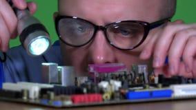 Mannelijke technicuskerel met glazen die computercomponenten inspecteren stock footage
