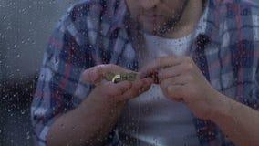 Mannelijke tellende muntstukken in wanhoop, die aan armoede en werkloosheid, depressie lijden stock videobeelden