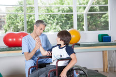 Mannelijke therapeut met jongen in rolstoel Stock Fotografie