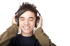 Mannelijke Tiener die aan muziek via hoofdtelefoon luistert stock afbeelding