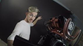 Mannelijke tiener influencer film zelf met een professionele camera in een studio voor zijn wekelijkse episode op videoblog - stock video