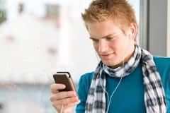 Mannelijke tiener met mp3 speler en earbuds Royalty-vrije Stock Foto's