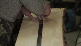 Mannelijke timmerman die met een heerser vóór het snijden van houten Raad meten stock footage