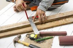 Mannelijke timmerman die met houten potlood en hulpmiddelen op het werkplaats werken Achtergrondvakmanhulpmiddel royalty-vrije stock afbeeldingen