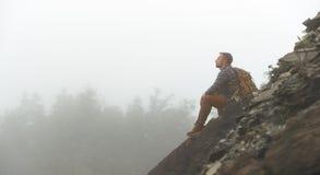 Mannelijke toerist bovenop berg in mist in de herfst royalty-vrije stock fotografie