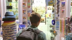Mannelijke toerist die aan herinneringswinkel komen, die giften met gelukkige glimlach op gezicht kiezen stock videobeelden