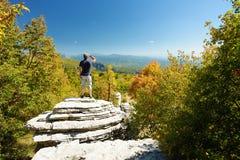 Mannelijke toerist die vorming van de Steen de bos, natuurlijke die rots onderzoeken, door veelvoudige die lagen van steen wordt  stock foto