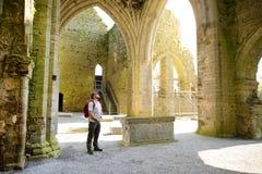 Mannelijke toerist in Jerpoint-Abdij, een geruïneerde Cisterciënzer die abdij, dichtbij Thomastown, Provincie Kilkenny, Ierland w stock afbeeldingen