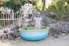 Mannelijke toerist in ronde blauwe vissersboot in Mui Ne, Vietnam stock afbeelding