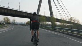 Mannelijke triathlete berijdende fiets als deel van zijn opleidingsprogramma Hij draagt zwarte uitrusting, helm en zonnebril Tria stock videobeelden