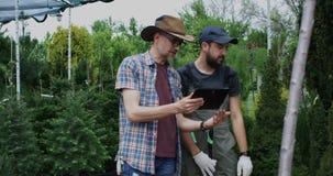 Mannelijke tuinlieden die tablet gebruiken stock video