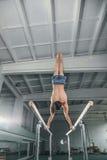 Mannelijke turner die handstand op brug uitvoeren Stock Foto's