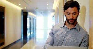 Mannelijke uitvoerende gebruikende laptop in gang stock video
