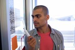 Mannelijke uitvoerende lezings kleverige nota's over glasdeur royalty-vrije stock afbeelding