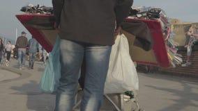 Mannelijke verkopende herinneringen voor toeristen in de straat van de kuststad, mensen het wandelen stock videobeelden