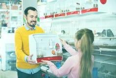 Mannelijke verkoper die kooi met kanarievogel tonen aan meisje in dierenwinkel stock foto's