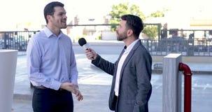Mannelijke verslaggever die een zakenman interviewen stock footage