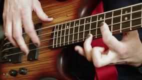 Mannelijke vingers dicht-u die solo op basgitaar spelen stock video