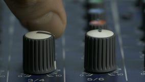 Mannelijke vingers die knoppen draaien op audio die bureau mengen stock video