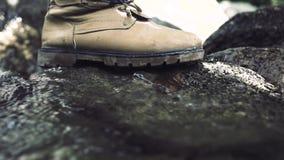 Mannelijke voet die op steen in stromende rivier stappen Mannelijke voet in schoen die langs rotsachtige bergrivier lopen in reis stock video