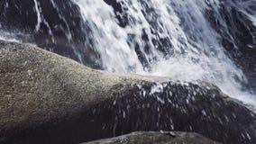 Mannelijke voet die op steen in stromende rivier van bergwaterval stappen Mannelijke voet in schoen die langs rotsachtige berg lo stock footage