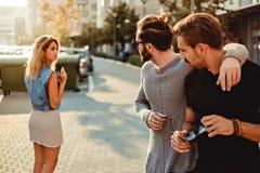 Mannelijke vrienden die het meisje in de straat bekijken stock afbeelding