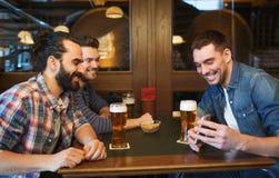 Mannelijke vrienden met smartphone het drinken bier bij bar Stock Afbeeldingen