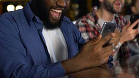 Mannelijke vrienden met smartphones die over favoriete teamoverwinning wordt opgewekt, die weddenschappen controleren stock video