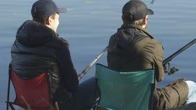 Mannelijke vrienden visserij, die bij het vouwen van stoelen, recreatieve activiteit zitten openlucht stock footage