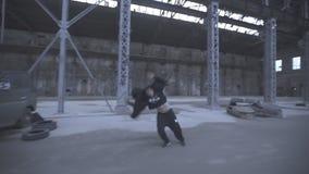 Mannelijke vrije agent die over auto springen en parkour trucs in een verlaten gebouw doen Kerel die acrobatische stunts tonen en stock video
