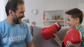 Mannelijke vrijwilligers realiserende droom die van weinig jongenswees, bokshandschoenen voorstellen stock footage