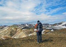 Mannelijke wandelaar die alleen in de wildernis wandelen die vulkanisch landschap met zware rugzak bewonderen Het avonturenzwerfl stock afbeelding