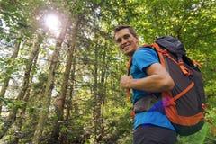 Mannelijke wandelaar die met grote rugzak aan camera glimlacht die door bomen en zonlicht wordt omringd stock foto