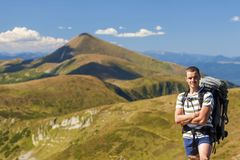 Mannelijke wandelaar die zich bovenop het rotsachtige piek het overzien berglandschap bevinden Royalty-vrije Stock Afbeeldingen