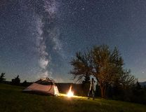 Mannelijke wandelaar enjoyng nacht die dichtbij toeristentent bij kampvuur onder blauwe sterrige hemel en Melkachtige manier kamp stock fotografie