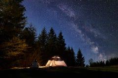 Mannelijke wandelaar enjoyng nacht die dichtbij toeristentent bij kampvuur onder blauwe sterrige hemel en Melkachtige manier kamp royalty-vrije stock afbeeldingen