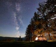 Mannelijke wandelaar enjoyng nacht die dichtbij toeristentent bij kampvuur onder blauwe sterrige hemel en Melkachtige manier kamp stock foto