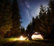 Mannelijke wandelaar enjoyng nacht die dichtbij toeristentent bij kampvuur onder blauwe sterrige hemel en Melkachtige manier kamp royalty-vrije stock fotografie