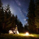 Mannelijke wandelaar enjoyng nacht die dichtbij toeristentent bij kampvuur onder blauwe sterrige hemel en Melkachtige manier kamp royalty-vrije stock foto's