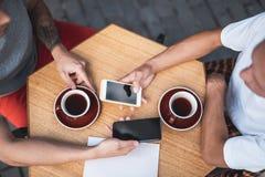 Mannelijke wapens die in mobiles in koffie typen stock fotografie
