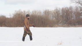 Mannelijke warme kleren die op het gebied met de jachtgeweer lopen stock footage