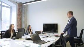 Mannelijke werknemersbesprekingen aan vrouwen die zich in bureau bevinden stock videobeelden
