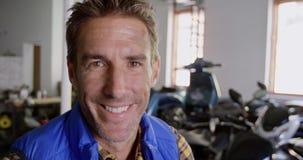 Mannelijke werktuigkundige die camera in de garage 4k bekijken van de motorreparatie stock footage