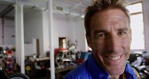 Mannelijke werktuigkundige die camera in de garage 4k bekijken van de motorreparatie stock video