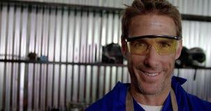Mannelijke werktuigkundige die camera in reparatiegarage 4k bekijken stock videobeelden