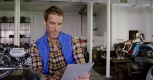 Mannelijke werktuigkundige die digitale tablet in de garage 4k gebruiken van de motorreparatie stock footage